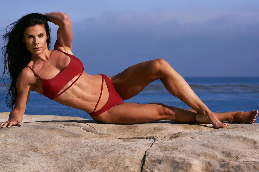 Camile Periat posing on a rock by the beach during a fitness photo shoot