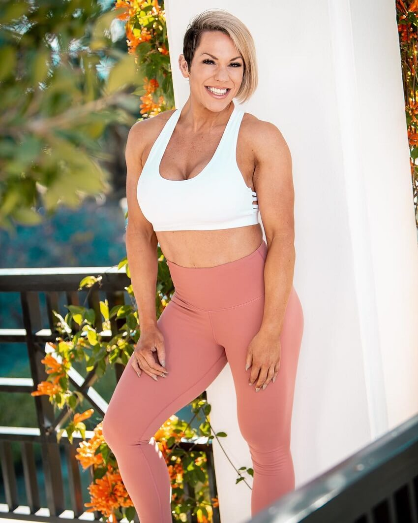 Carly Thornton posing by a wall outdoors, looking fit and lean