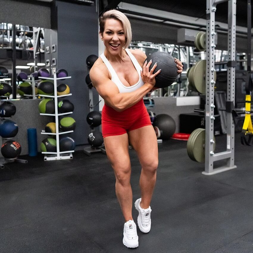 Carly Thornton posing with a medicine ball in the gym