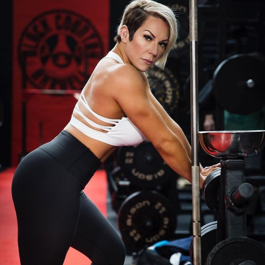 Carly Thornton posing in the gym leaning against the dumbbell rack