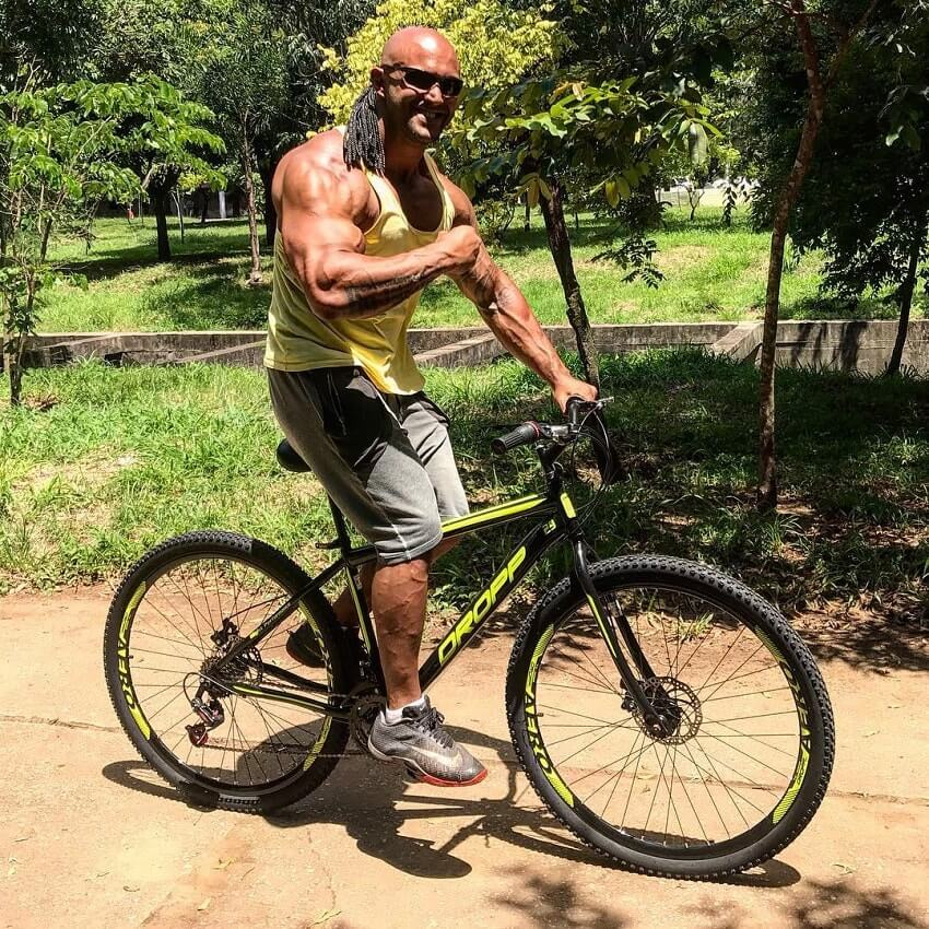 Danilo Franca flexing his arm while riding a bicycle