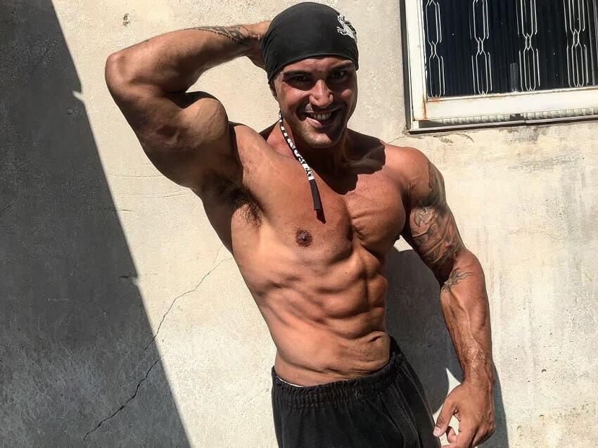 Danilo Franca flexing his abs while shirtless