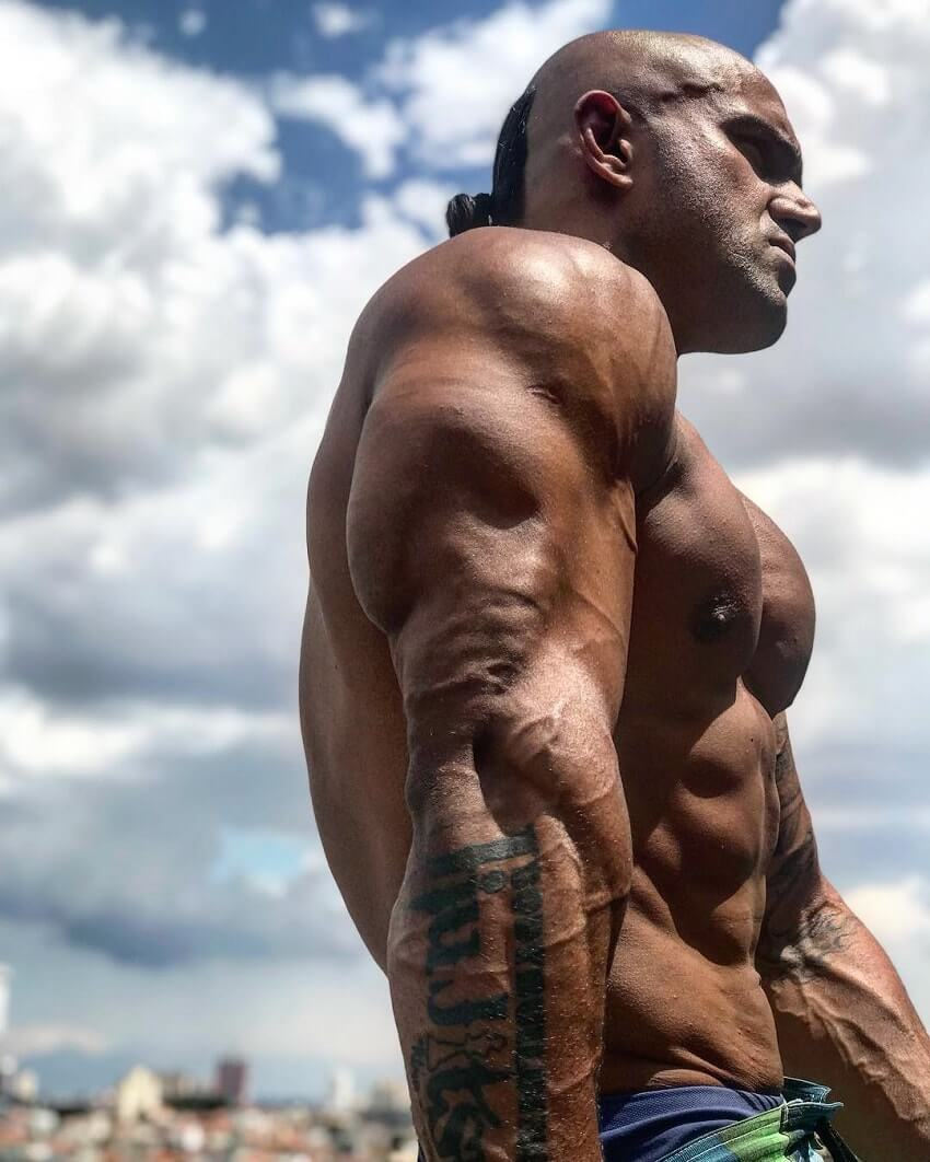 Danilo Franca flexing his ripped and bulging triceps outdoors