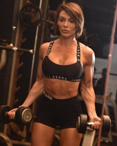 Danni Levy doing biceps curls in the gym