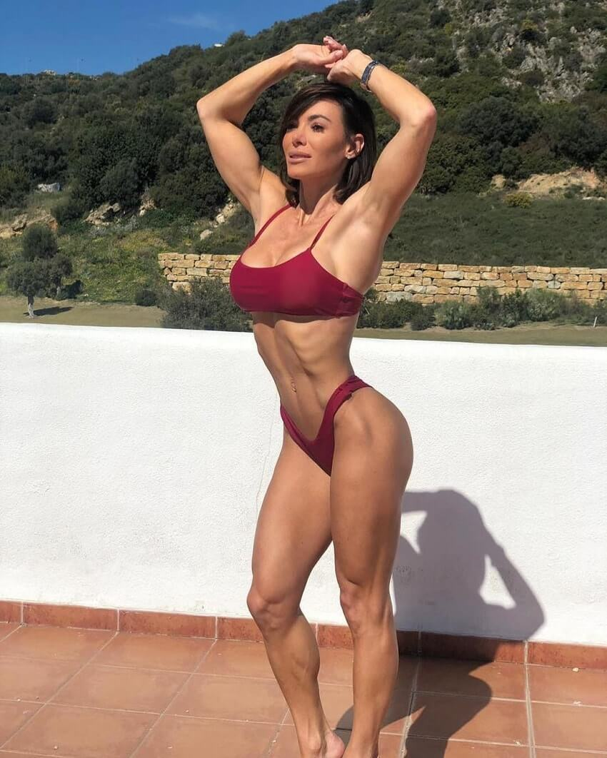 Danni Levy posing outdoors in a red bikini looking fit