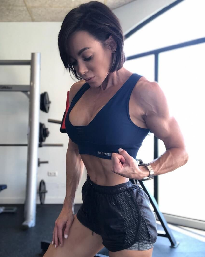 Danni Levy flexing her biceps in the gym