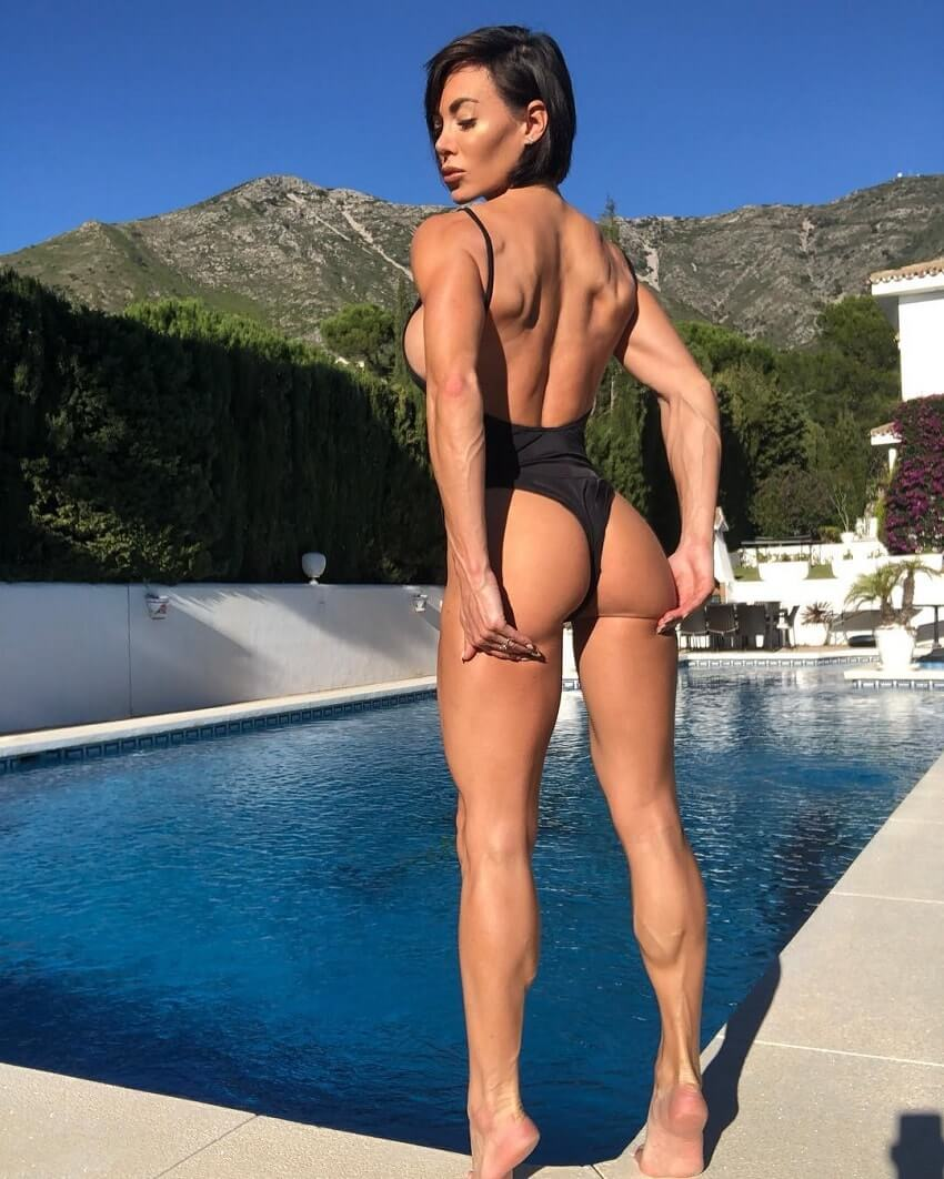 Danni Levy standing by a pool looking curvy and fit
