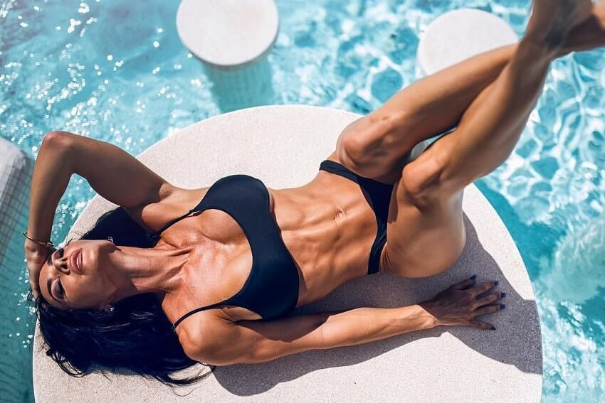 Danni Levy lying near a pool in her bikini looking fit and toned
