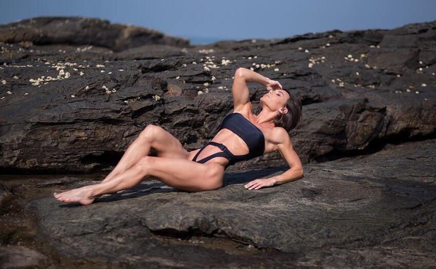 Danni Levy lying on a rock near a beach looking fit and lean