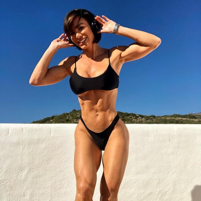 Danni Levy standing outdoors in a bikini, smiling and flexing her lean abs