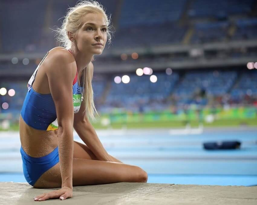 Darya Klishina sitting during a long jump contest in a huge stadium