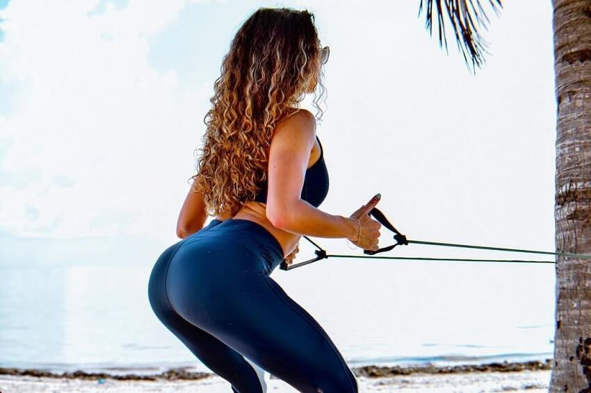 Diana Rinatovna doing a resistance bad exercise outdoors