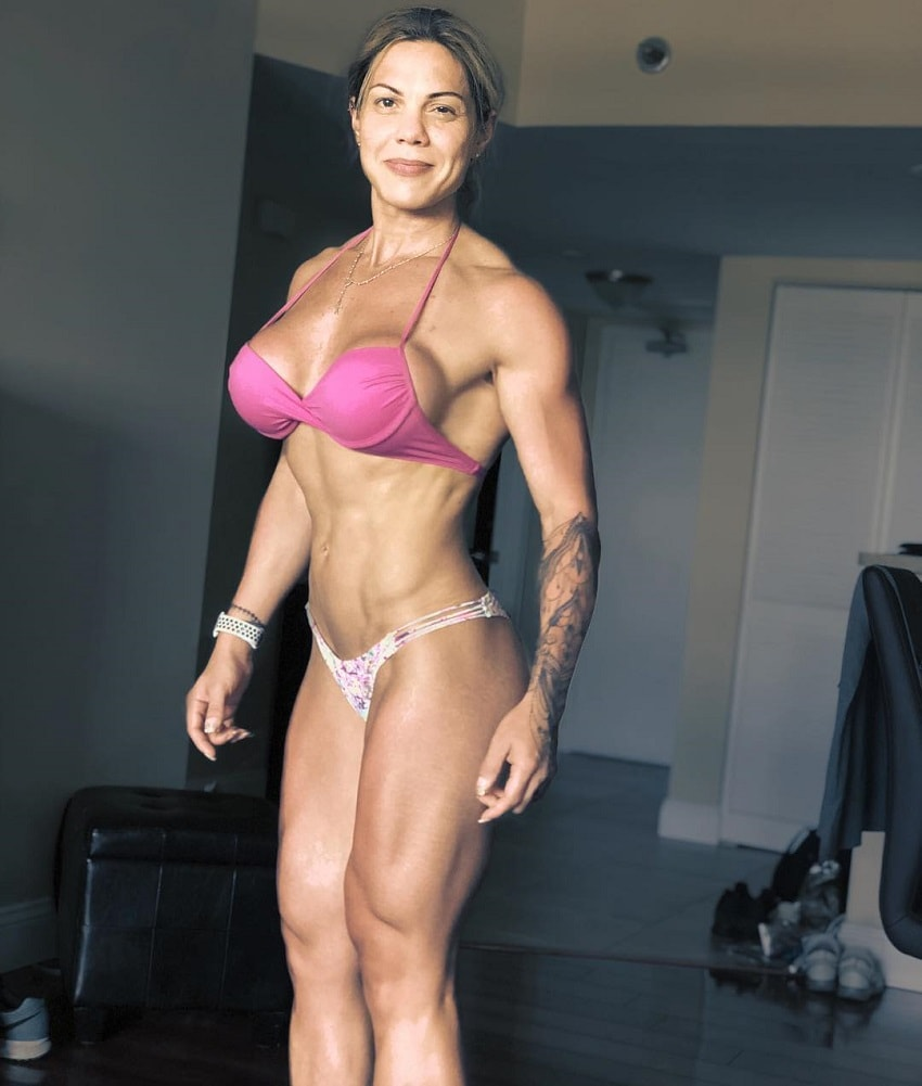 Dora Rodrigues posing in a bikini in her house, looking fit and curvy