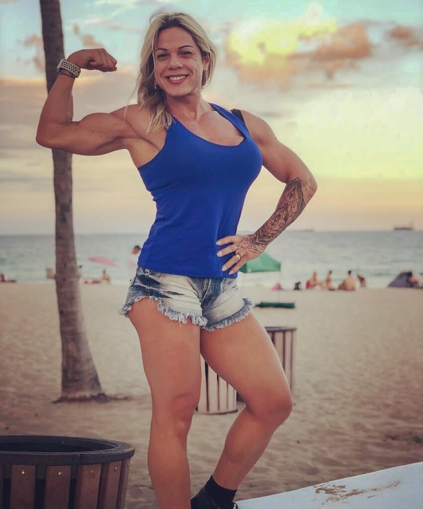 Dora Rodrigues flexing her biceps outdoors on a beach