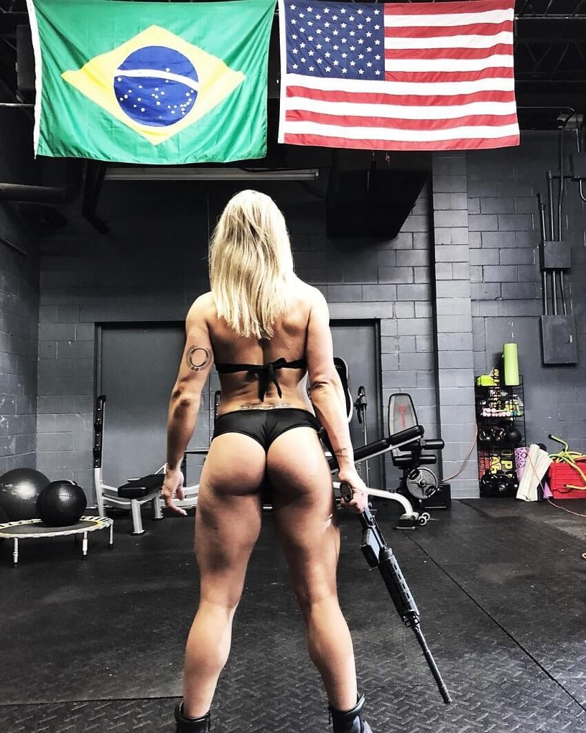 Dora Rodrigues posing with a gun in the gym, showing off her curvy glutes