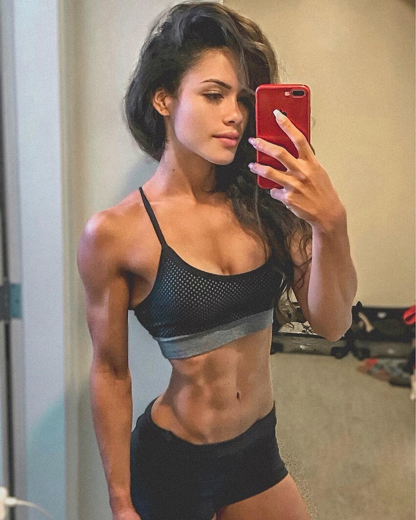 Etila Santiago taking a picture of her ripped physique
