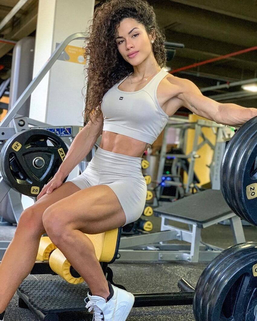 Etila Santiago sitting on a bench in a gym looking fit