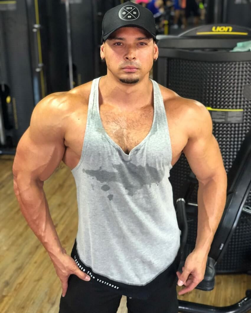 Felipe Franco posing in a grey tank top in the gym
