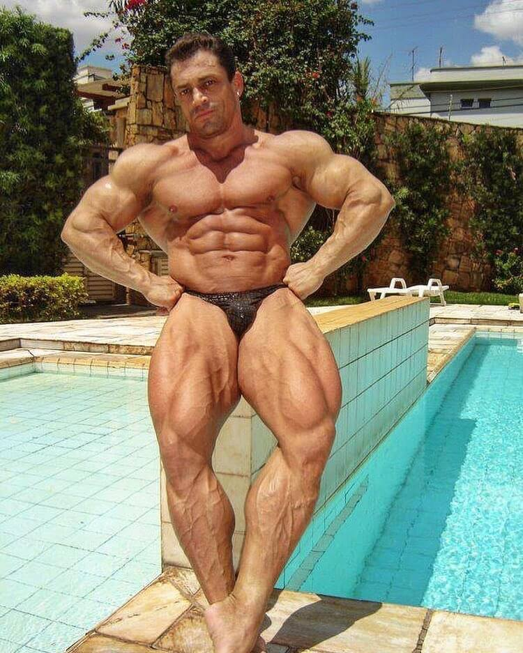 Fernando Sardinha when he was younger, posing shirtless by the pool, looking huge and ripped