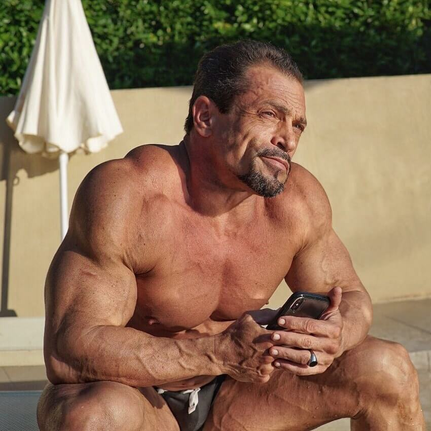 Fernando Sardinha sitting shirtless by the pool, looking ripped and big