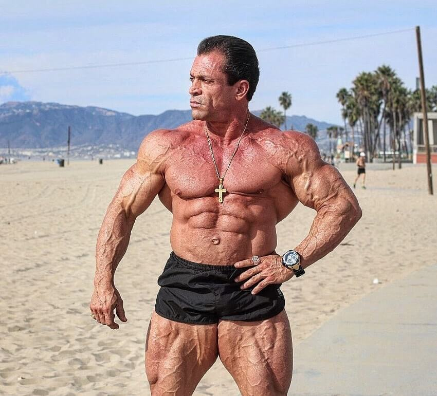 Fernando Sardinha standing shirtless on the beach, looking vascular and ripped