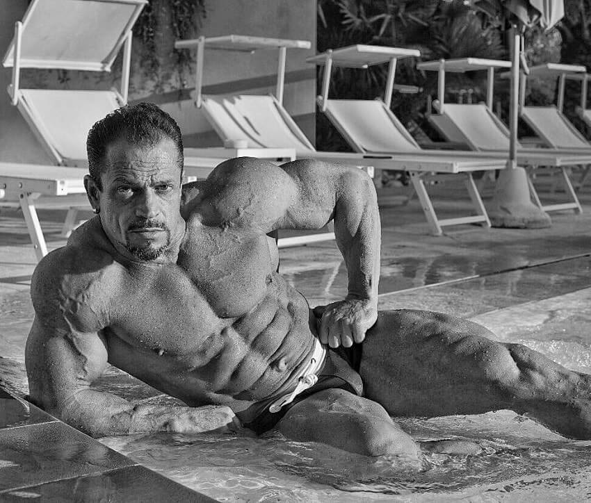 Fernando Sardinha posing shirtless by the pool, looking ripped