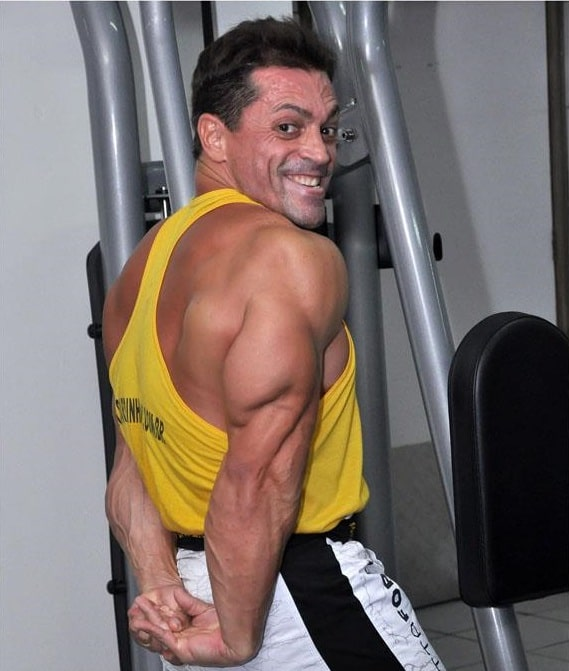 Fernando Sardinha flexing his triceps and smiling