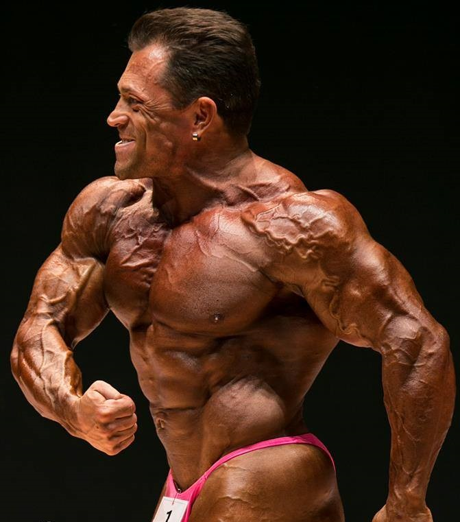 Fernando Sardinha posing side chest on the bodybuilding stage