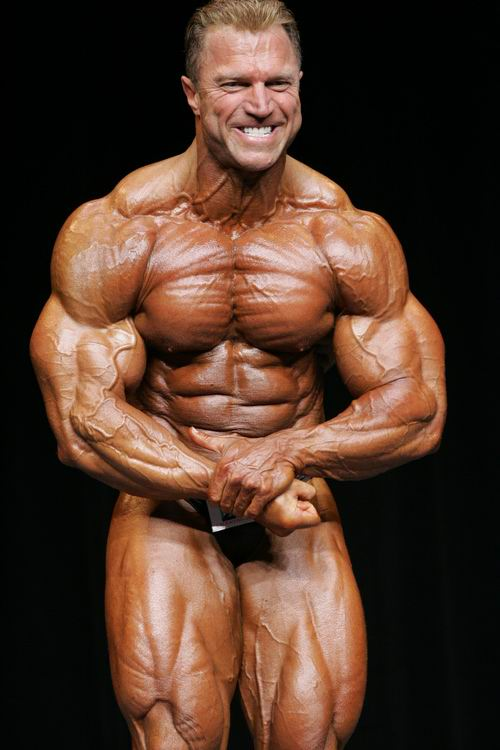 Gary Strydom flexing his swole and huge muscles in a bodybuilding competition