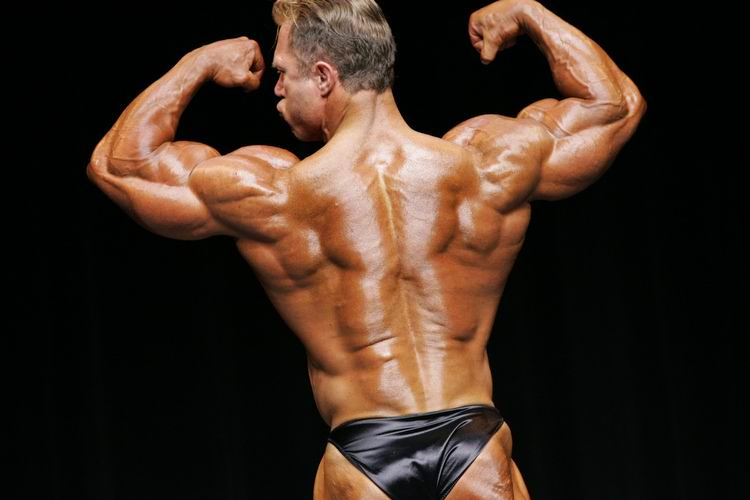 Gary Strydom performing back double biceps on the bodybuilding stage