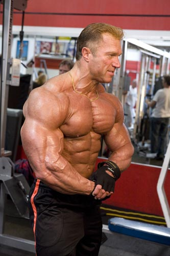 Gary Strydom posing shirtless in the gym, looking huge and ripped