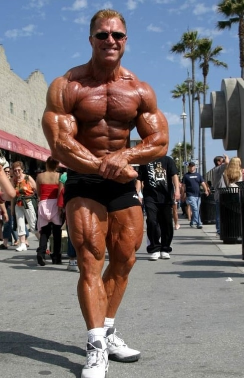 Gary Strydom flexing shirtless on the Venice beach with black sunglasses on