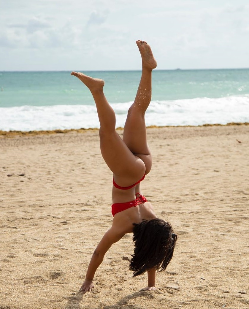 Johanna Sophia doing handstands on the beach, looking fit and lean
