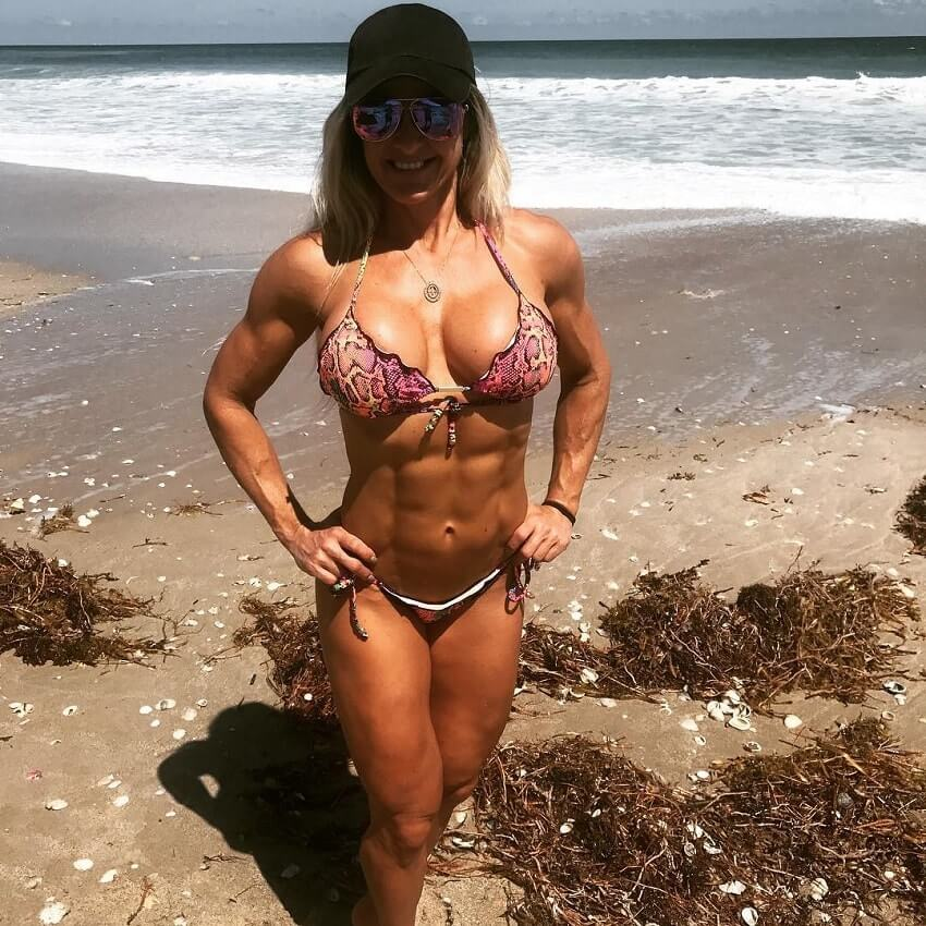 Karen Domingos standing on the beach in a bikini, looking fit and lean