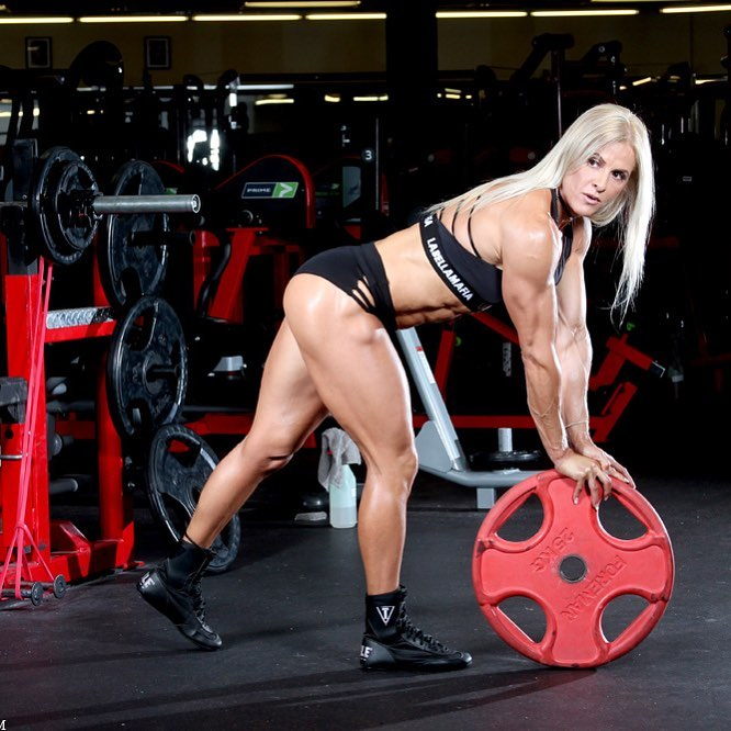 Karen Domingos posing with weights in the gym