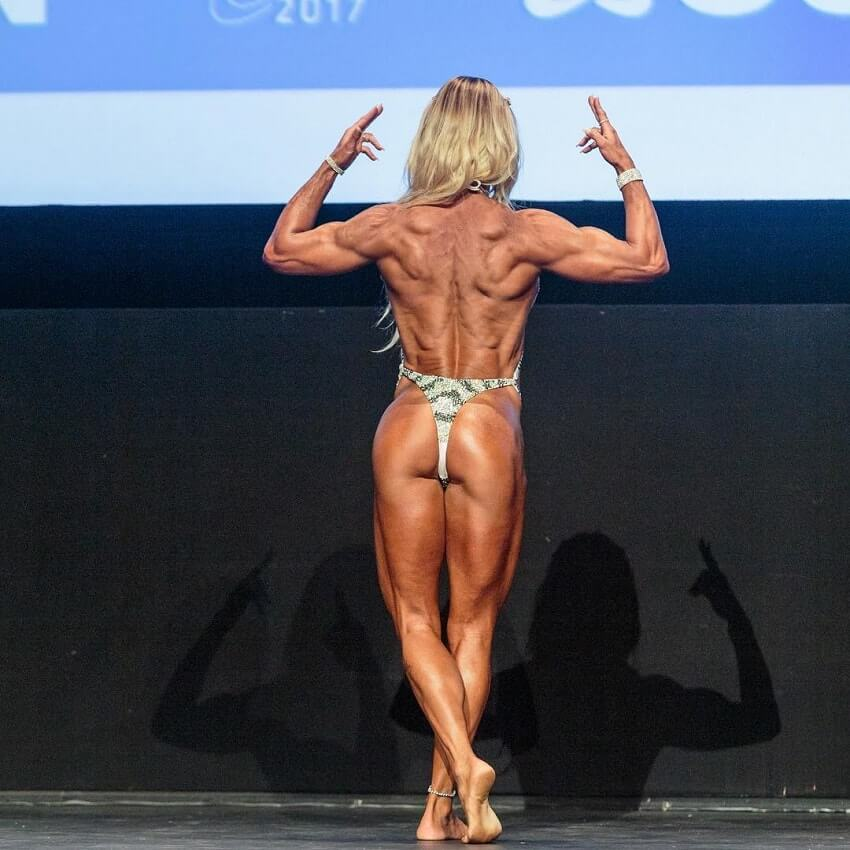 Karen Domingos posing on the fitness and figure stage looking ripped