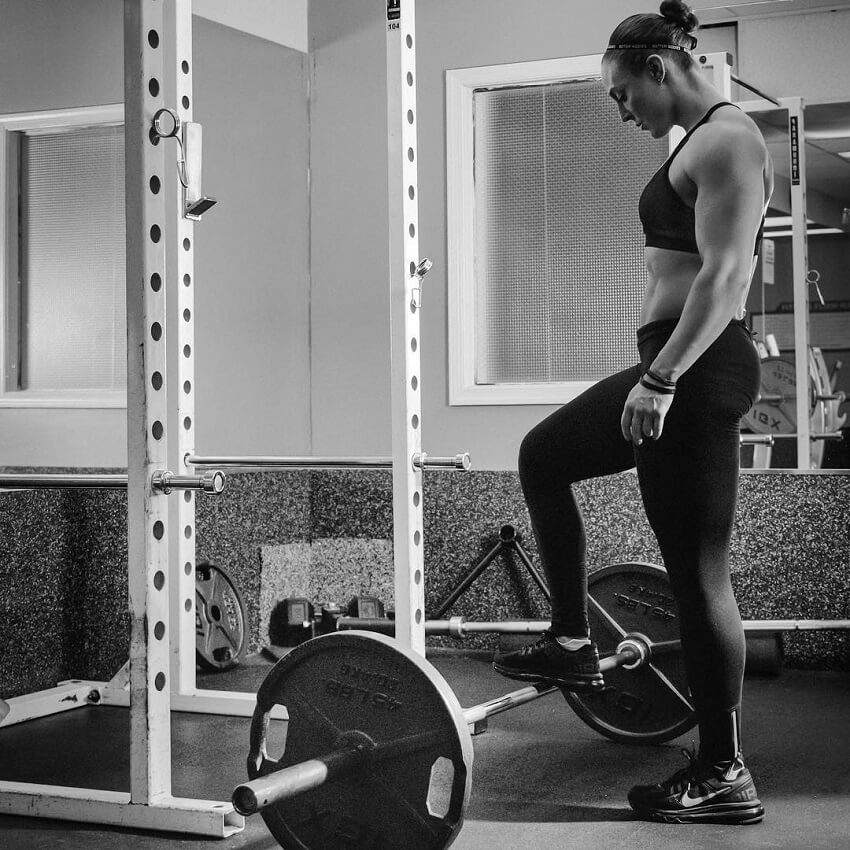 Katie Lee standing by a squat rack in the gym