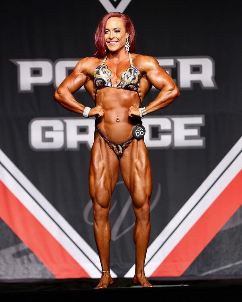 Katie Lee posing on the Women's Physique stage