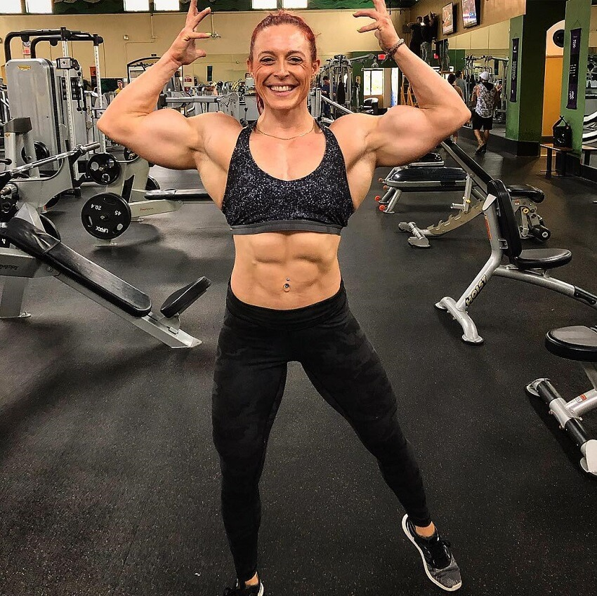 Katie Lee flexing and smiling in a gym
