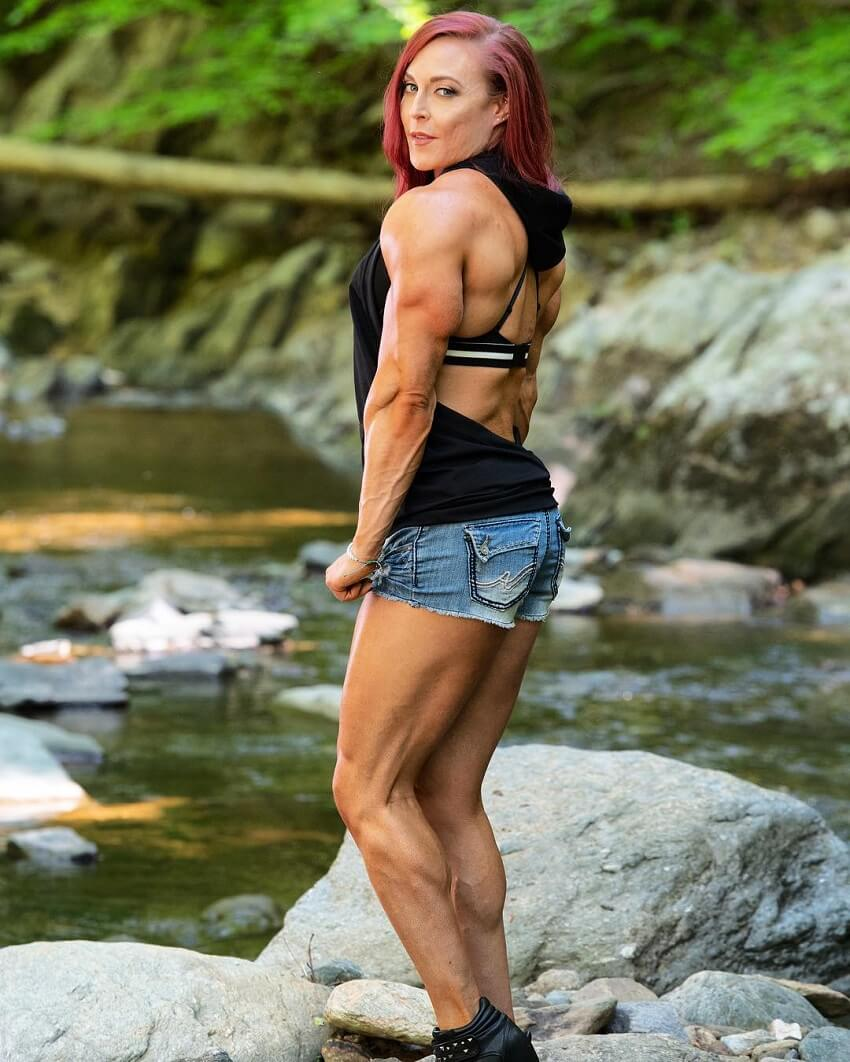Katie Lee standing by a creek in nature, looking fit and aesthetic