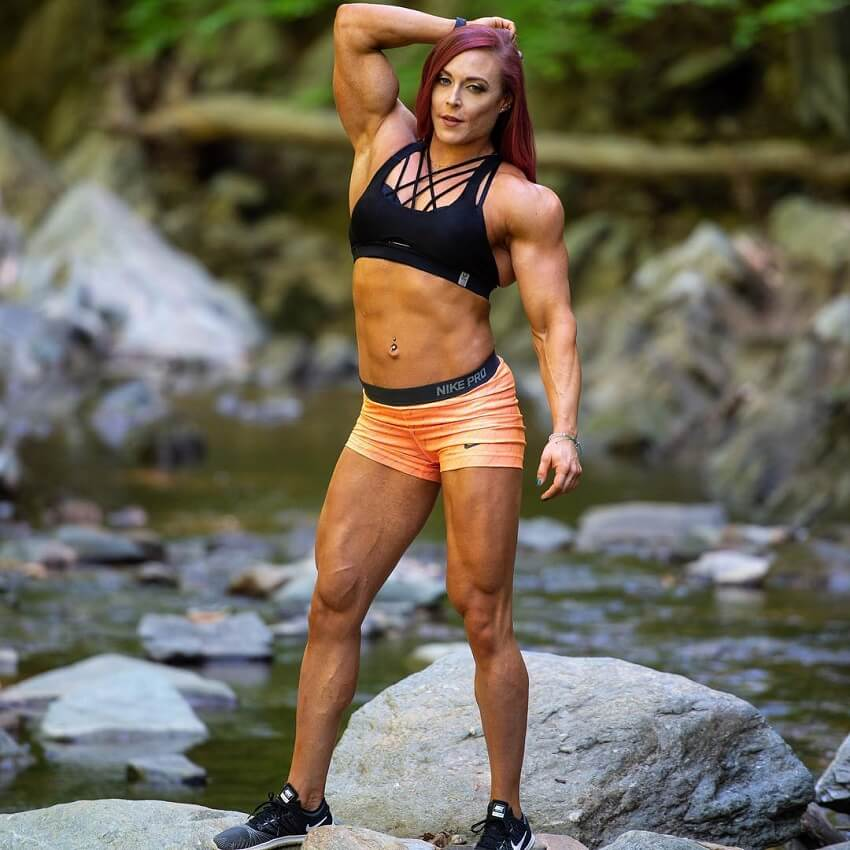 Katie Lee standing on a rock by a creek, looking fit and lean