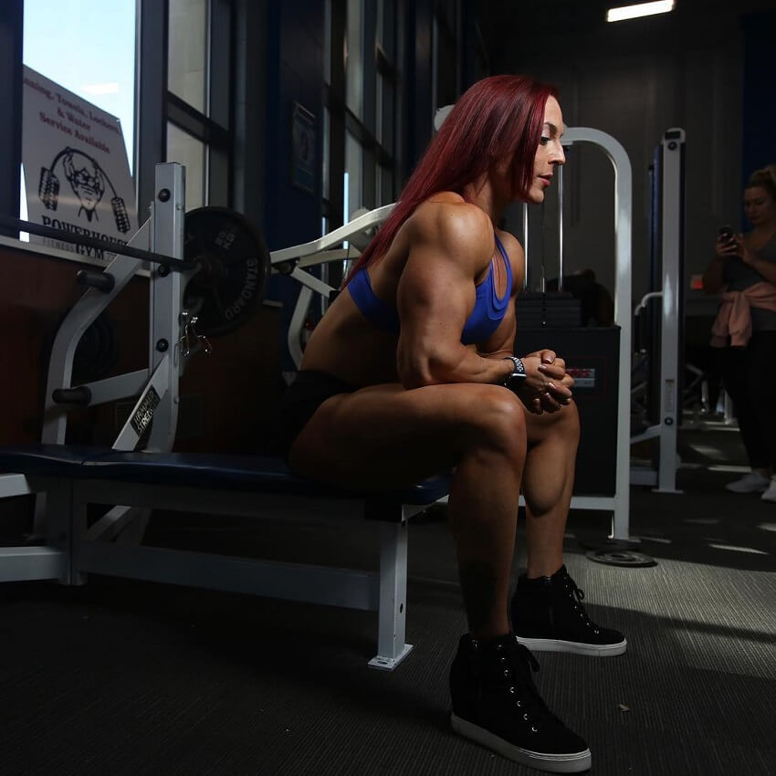 Katie Lee sitting on a bench in the gym, looking fit and strong
