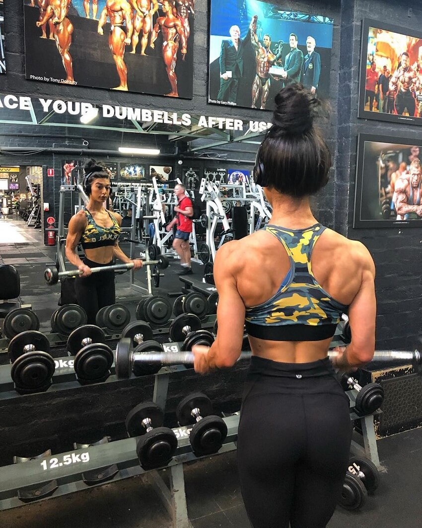 Lauralie Chapados doing barbell bicep curls in front of a dumbbell rack in a gym