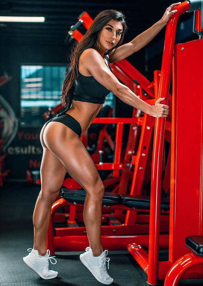 Lauralie Chapados posing in a gym during a fitness photo shoot looking curvy and fit