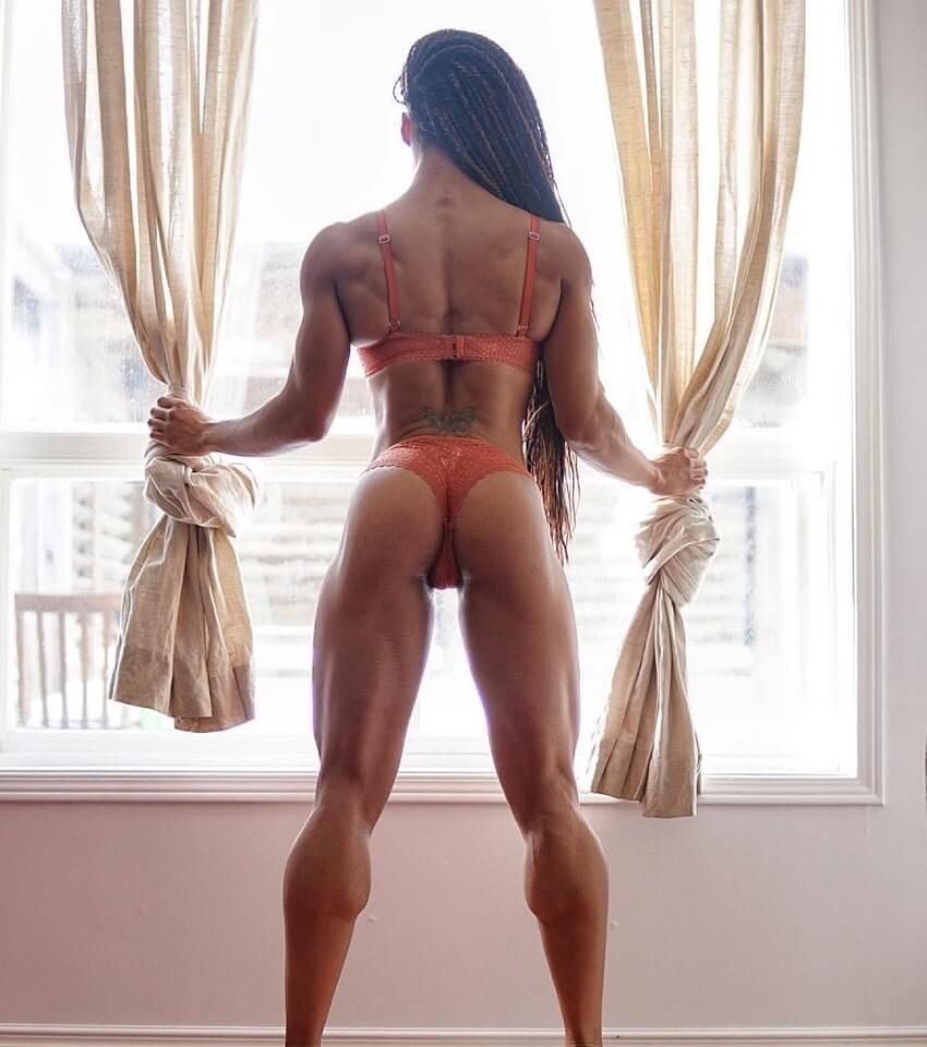 Lola Montez showing off her curvy glutes and muscular back while looking through a balcony during a fitness photo shoot
