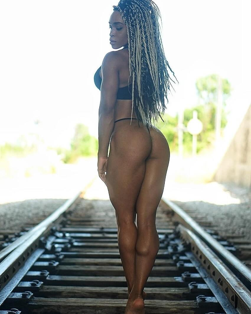 Lola Montez standing on trail rails posing in a fitness photo shoot