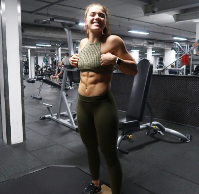 Lucy Davis flexing her abs in the gym