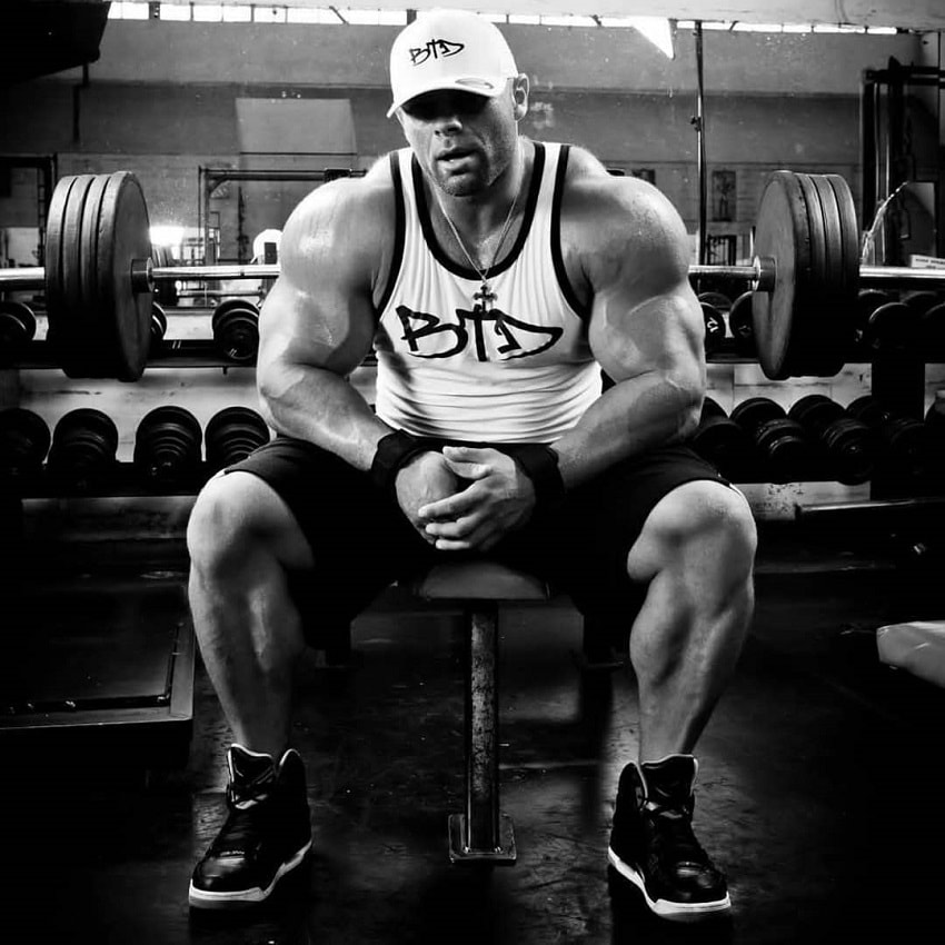 Marius Dohne sitting on a bench in the gym, looking big and strong