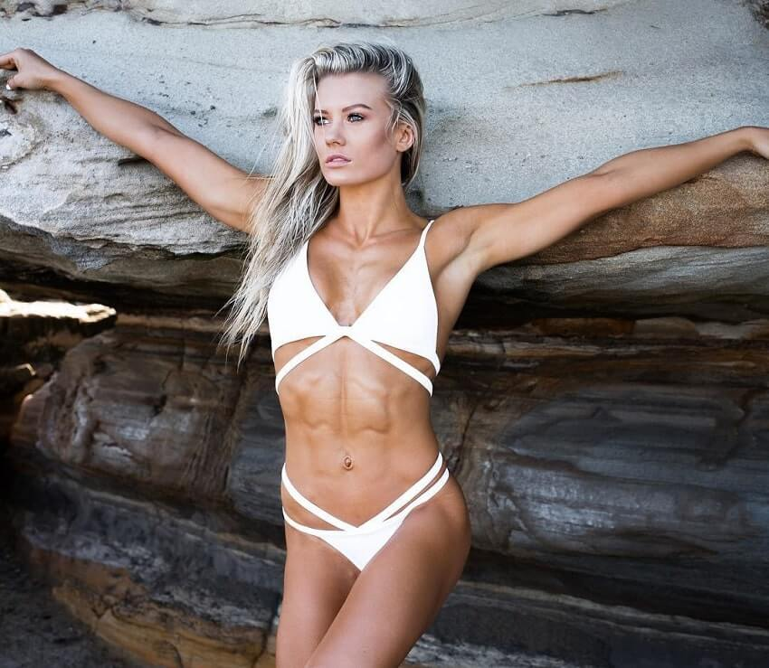 Micky Parker leaning against a rock wearing a white bikini during a fitness photo shoot
