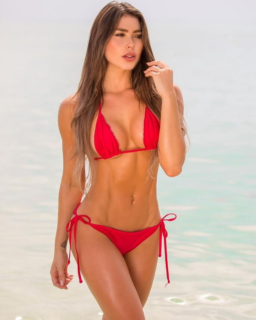 Paola Canas walking down the beach in a red swimsuit, looking fit and lean